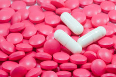 Biały medyczne kapsuły na obfitości czerwonym pigułek backgro Fotografia Stock