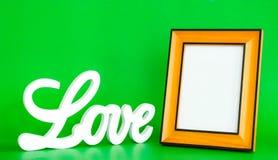 Biały miłość znak i pusta obrazek rama na zielonym tle Zdjęcia Royalty Free