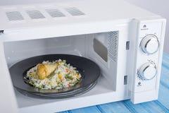 Biały mikrofala piekarnik na błękitnej drewnianej powierzchni dla grzejnego jedzenia, Fotografia Stock
