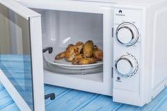 Biały mikrofala piekarnik na błękitnej drewnianej powierzchni dla grzejnego jedzenia, Obraz Royalty Free