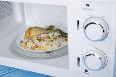 Biały mikrofala piekarnik na błękitnej drewnianej powierzchni dla grzejnego jedzenia, Obrazy Royalty Free