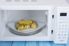 Biały mikrofala piekarnik na błękitnej drewnianej powierzchni dla grzejnego jedzenia, Zdjęcia Royalty Free