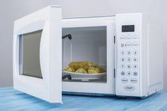 Biały mikrofala piekarnik na błękitnej drewnianej powierzchni dla grzejnego jedzenia, Zdjęcie Stock
