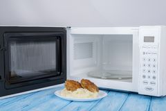 Biały mikrofala piekarnik na błękitnej drewnianej powierzchni dla grzejnego jedzenia, Zdjęcia Stock