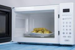 Biały mikrofala piekarnik na błękitnej drewnianej powierzchni dla grzejnego jedzenia, Obrazy Stock