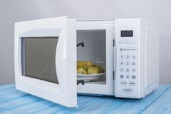 Biały mikrofala piekarnik na błękitnej drewnianej powierzchni dla grzejnego jedzenia, Obraz Stock