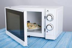 Biały mikrofala piekarnik na błękitnej drewnianej powierzchni dla grzejnego jedzenia, Fotografia Royalty Free