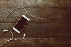 Biały mo żółci telefon z słuchawkami na biurowym biurku i c Zdjęcia Stock