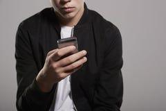 Biały nastoletni chłopak używa telefon komórkowego, w połowie sekci uprawa zdjęcie stock