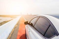 Biały nowy samochód na autostrady drodze z słońca światłem Fotografia Stock