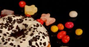 Biały oszklony pączek z czekoladą, lodowacenie lub kropi, paskował karmel cukierki, kolorowego dragee z rodzynkami lub arachidy zbiory