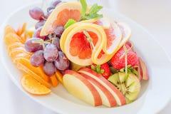 Biały owoc talerz z truskawką, grape-fruitem, winogronami, pomarańcze, ziele i serem, Zamyka w górę wizerunku z selekcyjną ostroś Obraz Royalty Free
