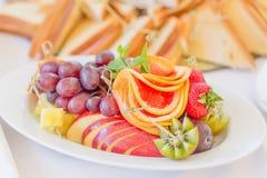 Biały owoc talerz z truskawką, grape-fruitem, winogronami, pomarańcze, ziele i serem, Zamyka w górę wizerunku z selekcyjną ostroś Obrazy Royalty Free