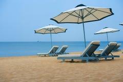 Biały parasol na morze plaży i sunbeds fotografia stock