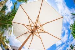 Biały parasolowy tła niebieskie niebo na tropikalnej biel plaży Fotografia Stock