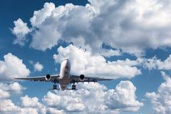 Biały pasażerski samolot lata w niebieskim niebie z chmurami Obrazy Stock