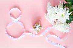 Biały prezenta świętowania faborek w 8 cyfr kształcie nad różowym tłem Fotografia Royalty Free