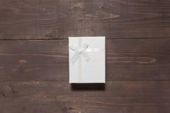 Biały prezenta pudełko jest na drewnianym tle z pustą przestrzenią Zdjęcie Royalty Free