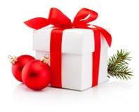 Biały prezenta pudełko wiązał czerwonego tasiemkowego łęku i dwa bożych narodzeń bauble Isol obraz stock