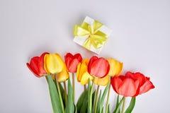Biały prezenta pudełko z żółtego tasiemkowego pobliskiego bukieta żółtym czerwonym tulipanem Zdjęcie Royalty Free