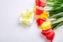 Biały prezenta pudełko z żółtego tasiemkowego pobliskiego bukieta żółtym czerwonym tulipanem Fotografia Stock