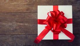 Biały prezenta pudełko z czerwonym faborku i łęku tłem Zdjęcia Stock