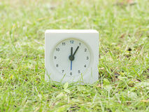 Biały prosty zegar na gazonu jardzie, 12:05 dwanaście pięć Fotografia Royalty Free