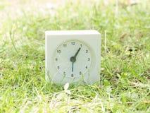 Biały prosty zegar na gazonu jardzie, 1:05 jeden pięć Obrazy Royalty Free