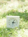 Biały prosty zegar na gazonu jardzie, 3:05 trzy pięć Zdjęcia Royalty Free