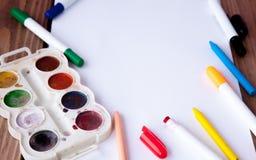 Biały prześcieradło papier kłaść na drewnianym stole, ołówkach, farbach i markierach, blisko, tylna szkoły ilustracyjny biura szk zdjęcie royalty free
