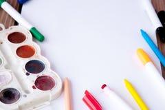 Biały prześcieradło papier kłaść na drewnianym stole, ołówkach, farbach i markierach, blisko, tylna szkoły ilustracyjny biura szk zdjęcie stock