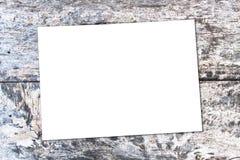 Biały prześcieradło papier na dębowym brązu stole Obraz Stock