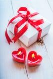 Biały pudełko z czerwonym faborkiem, czerwone świeczki w formie serca ro Obraz Royalty Free