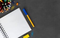 Biały puste miejsce spirali papieru notatnik z piórem, barwioni ołówki, gumka, papierowa kępa, papierowe klamerki na pustym  zdjęcia royalty free