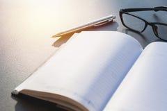 Biały pusty notatnik, podręcznik z szkłami i pióro na stołowym dowcipie, obraz royalty free