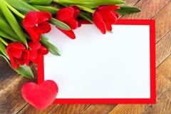 Biały pusty prześcieradło w czerwieni ramie, czerwonych tulipanach i pluszowym sercu na ru, zdjęcie royalty free