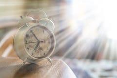 Biały retro budzik na nightstand przy rankiem f zdjęcie stock