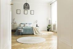 Biały round dywanik w przestronnym sypialni wnętrzu z zielonym łóżkowym unde obraz stock