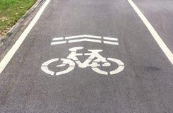 Biały rowerowego pasa ruchu znak na drodze Zdjęcia Stock