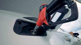 Biały samochód dostaje refilled benzynową krócicą z czerwoną rękojeścią zbiory wideo