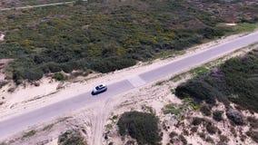 Biały samochód jedzie wzdłuż drogi w pustyni zbiory