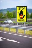 Bia?y samoch?d na autostradzie w austriackiej wsi z przerw?, fa?szywym znakiem ostrzega? kierowc?w STOP/FALSCH/ fotografia royalty free