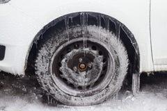 Biały samochód z zamarzniętymi oponami stoi w zimie obraz stock