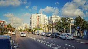 Biały samochodowy poruszający na szerokiej drodze w mieszkaniowym okręgu Obrazy Royalty Free