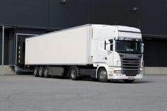 Biały Scania Semi ciężarówki rozładunek przy Magazynowym budynkiem