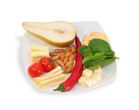 Biały serowy talerz z migdałami, czerwoni pieprze Obrazy Royalty Free