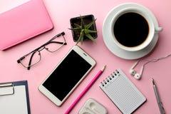 Biały smartphone i dostawy na jaskrawym różowym tle filiżanka kawy i biurowych na widok fotografia royalty free