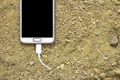 Biały smartphone z ładowarką czopował w piasek frontowy i tylny tło zamazujący zdjęcia stock