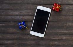 Biały smartphone z prezentami na nieociosanym drewnianym stole Czarny parawanowy smartphone na podławym modnym tle fotografia royalty free