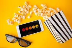 Biały smartphone z smilies na ekranie, 3d szkłach, czarny i biały pasiastym papierowym pudełku i rozrzuconym popkornie, obrazy royalty free